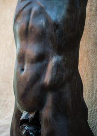 Beech bum. A bronze resin cast sculpture of a male torso in the round.