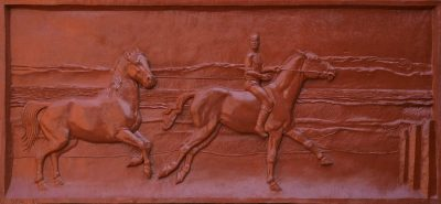 Ferring beach. A resin cast of a detailed relief sculpture showing ponies being exercised on a beach.