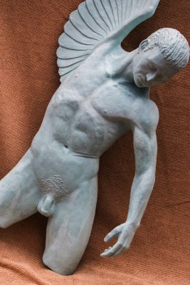 Fly or fall. A resin cast sculpture of a male nude with one downcast arm and one unfurled wing, caught between flight and falling.